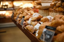 Image of a lot of sweet croissants in supermarket bakery