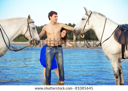 Image of a man and a woman in love with the sea with horses - stock photo