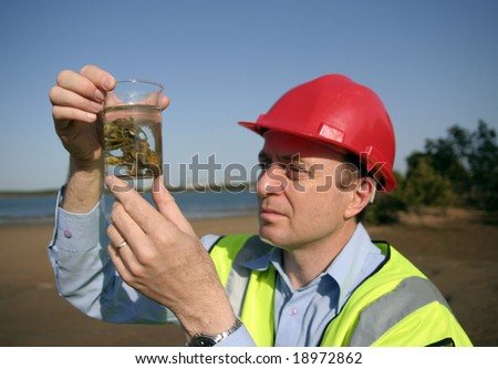 Image of a man holding on to a glass beaker with an environmental sample