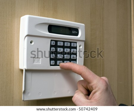 Image of a man setting a burglar alarm