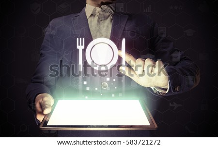Image of a man with tablet in his hands and food restaurant icon. He looking menus, ordering food delivery, rate restaurant with using online services.
