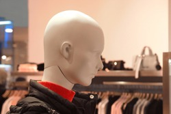 Image of a mannequin in a jacket and sweater in a boutique
