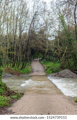 Image of a mountain road flooded by the flood of a river, with sand and rubble around
