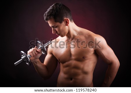 Image of a muscular young man lifting weights on black background