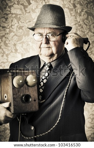 Image of a old fashioned vintage business man standing in a office communicating to the exchange through a retro box telephone in a technology concept
