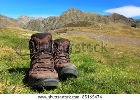 Image of a pair of hiking boots lying in the grass in front of a beautiful mountainous landscape in Pyrenees Mountains.