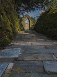Image of a path leading to a stone archway
