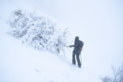 IMAGE OF A PERSON HIKING IN EXTREME CONDITIONS. ALPINIST TREKKING IN HARSH WINTER CONDITIONS. COLD AND BAD WEATHER CONCEPT.