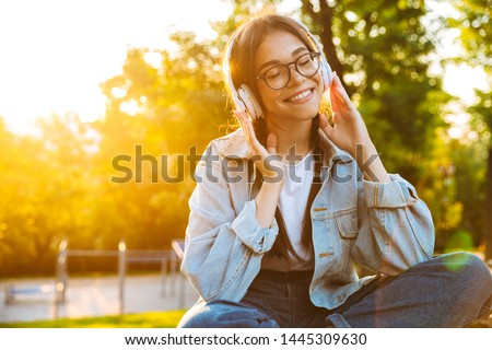 Image of a pleased happy young teenage girl student sitting outdoors in beautiful green park listening music with headphones.