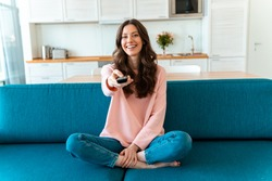Image of a positive smiling optimistic young woman sit indoors at home watch tv holding remote control on sofa.