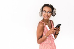 Image of a positive young african woman with dreads posing isolated over white wall background using mobile phone chatting looking away.