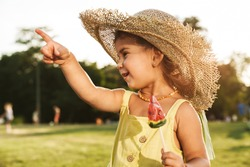 Image of a positive young cutie little girl eat lollipop candy outdoors in nature green park pointing.
