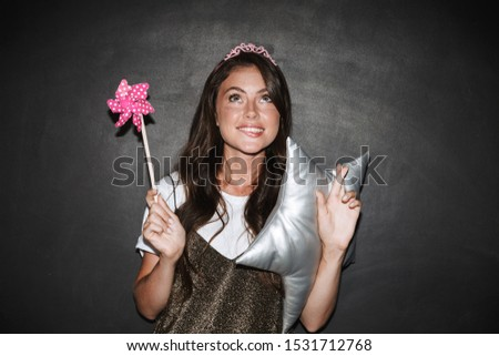 Image of a pretty cute nervous girl with pillow and toy magic wand isolated over chalkboard grey background make hopeful please gesture.