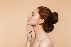 Image of a pretty young redhead woman posing isolated over beige wall background. Eyes closed.