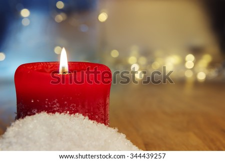 Image of a red burning candle with bokeh lights in background and free space