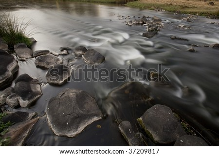 Image of a river taken in autumn with a slow shutter speed - stock photo