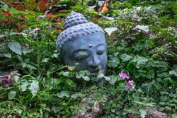 Image of a sleeping buddha grey-blue stone sculpture laying peacefully in a bright green vibrant garden among pink flowers on the East coast of Barbados, the Caribbean, at botanical gardens.