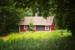 Image of a small red cottage in a forrest clearing. South east Sweden.