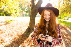 Image of a smiling cutie young student redhead girl in autumn park using mobile phone.