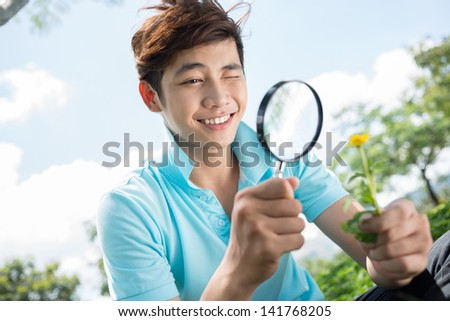 Image of a teenager looking at the flower through the magnifier outside