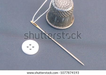 image of a thread, needle, thimble