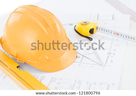 Image of a typical engineer workplace with blueprint, hardhat and measuring tools