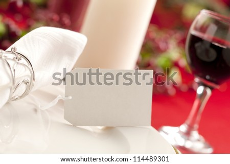 Image of a white plate with table napkin and a blurred wine glass on the side on holiday season