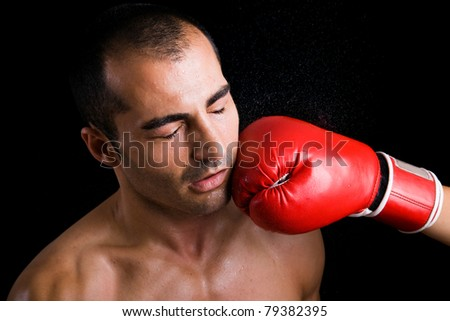 Image of a young boxer man getting punched in the face over black background