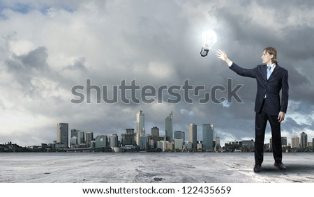 Image of a young businessman holding a shining light bulb