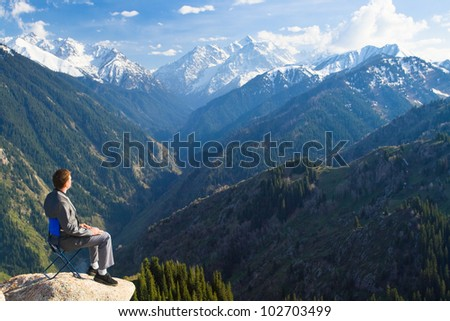 Image of a young businessman who sits on a chair at the top of the mountain and looks into the distance to the beautiful mountains, thinking about future plans.