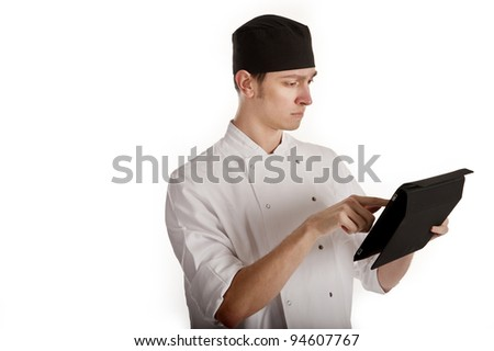 Image of a young chef making full use of modern technology using a computer tablet to assist with his work - either to refer to a recipe, conduct stock checks, make orders to suppliers etc - stock photo