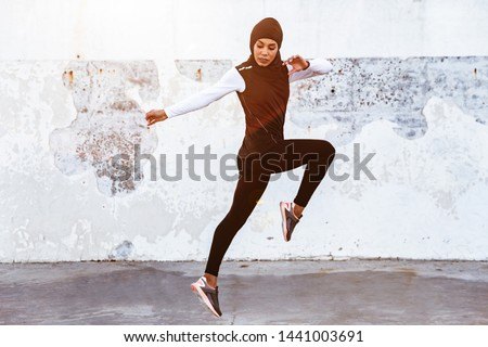 Image of a young concentrated muslim sports fitness woman dressed in hijab and dark clothes posing make sport stretching exercises outdoors at the street running.