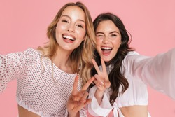 Image of a young emotional smiling friends women posing isolated over pink wall background take selfie by camera showing peace gesture.
