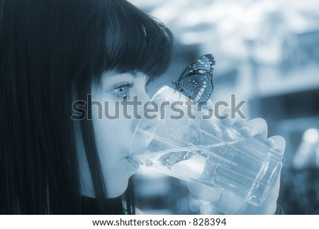 Image of a young girl drinking water with a butterfly perched on the glass