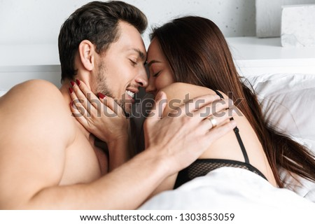 Image of a young loving couple indoors in home in bed lies hugging and kissing.