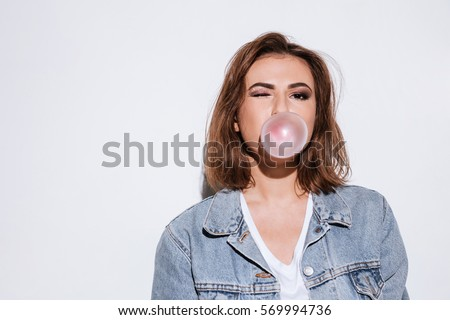Image of a young playful lady dressed in jeans jacket standing isolated over white background while blowing bubble with chewing gum. Look at camera.