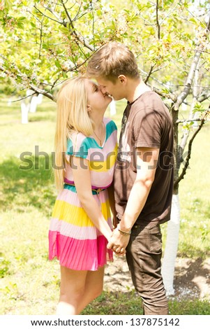 Image of a young romantic couple holding hands and kissing while on an outdoor date.