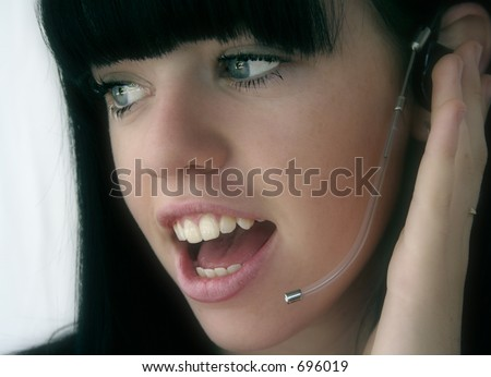 Image of a young woman answering a call from a customer - stock photo