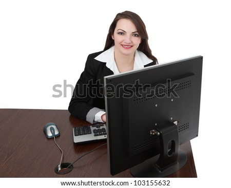 Image of a young woman in front of a computer at her workplace looking to the camera and smiling, isolated against a white background.