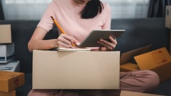 Image of a young woman Sales online, see the tablet, taking notes at home.