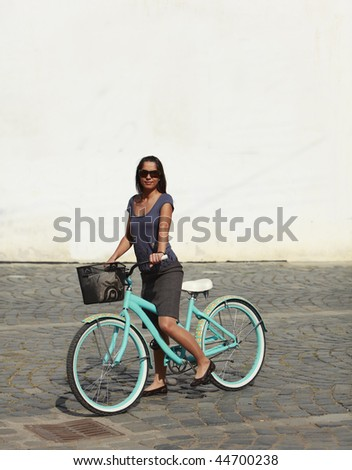 Image of a young woman standing with her bicycle in a paved street of a city in front of a white building wall.