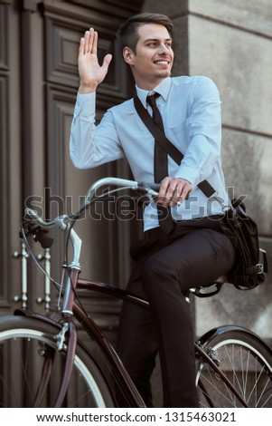 Image of a young young handsome businessman riding bicycle.