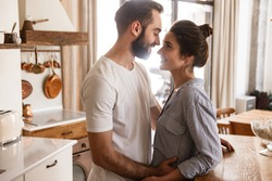 Image of adorable brunette couple in love man and woman 20s smiling while hugging together in apartment