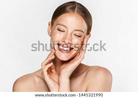 Image of adorable half-naked woman smiling at camera with eyes closed and touching her face isolated over white background