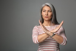 Image of adult mature woman wearing striped shirt doing stop or denial gesture isolated over gray background