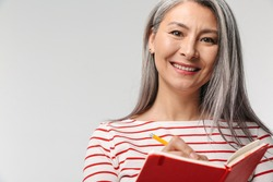 Image of adult mature woman with long white hair holding diary book and pen isolated over gray background