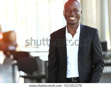 Image of African-American business leader looking at camera in working environment