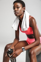 Image of african american sportswoman with towel drinking water while sitting isolated over white background