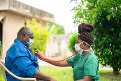image of african man with face mask, braided black woman in face mask  holding stethoscope- home health care concept