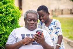 image of African old man and young girl, with smart phone-outdoor concept